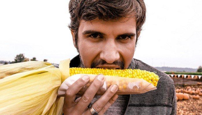 Mann beisst in Maiskolben; veganes Essen