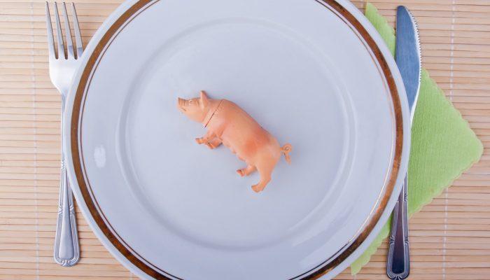 Plastikschwein auf Teller samt Besteck - Fleischverzehr sinkt