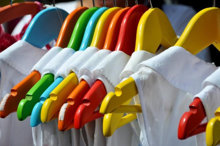 Vegane, weiße Kleidung auf bunten Bügeln